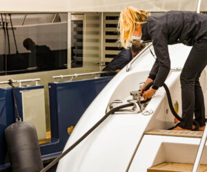 Crew member securing a rope to a luxury yacht